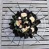 Creatief bloemschikken met rozen uit de tuin en donkere bladeren van de Cotinus