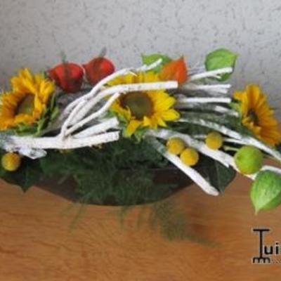 Tafelstuk met zonnebloemen tussen takken.